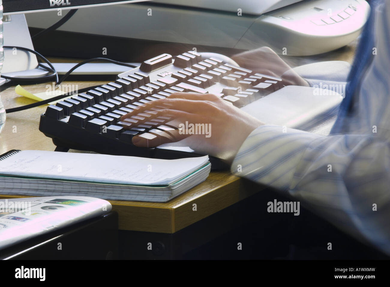 Blurred fingers using computer keyboard - Stock Image