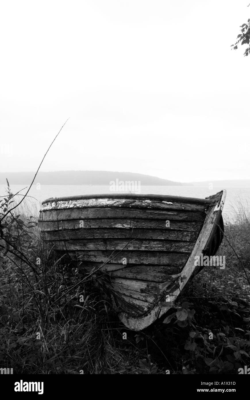 abandoned boat on stone beach deserted lonely desolate northern sweden lake swedish wood rot decay - Stock Image