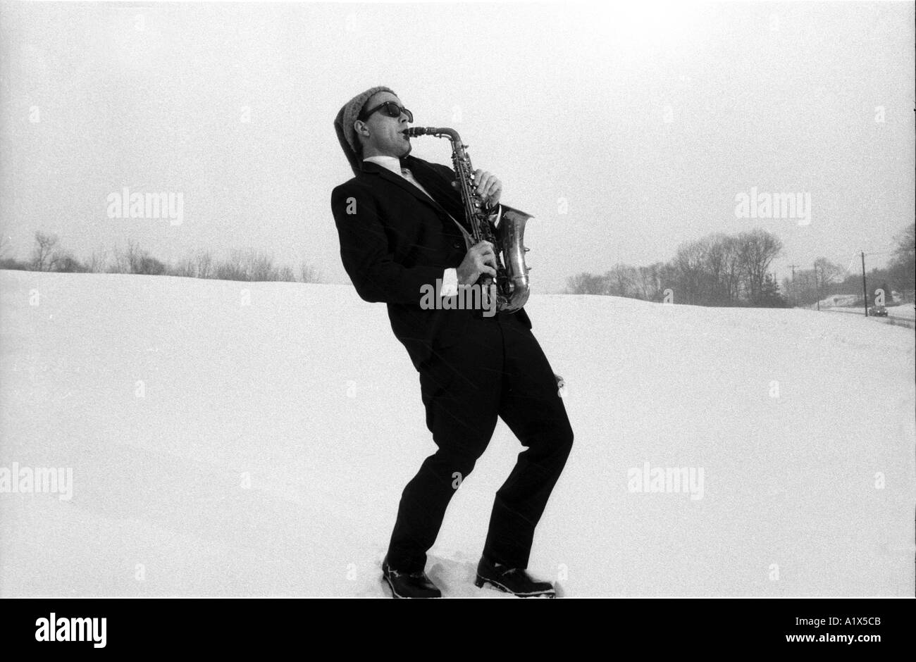Man playing saxophone in a snow storm Winter blues Funny concept wearing Christmas holiday hat - Stock Image