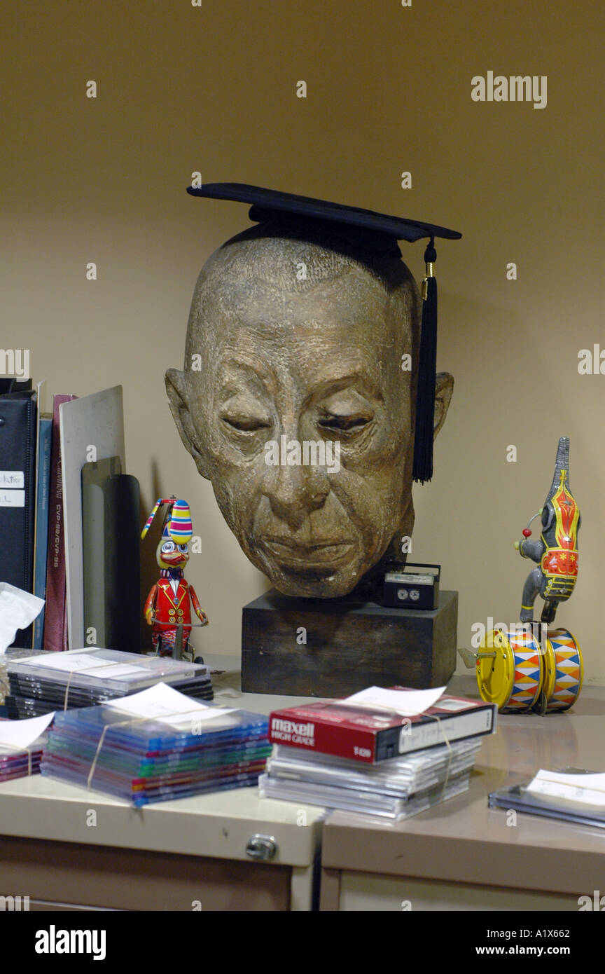 A strange asian man head statue with graduation cap on it and office  supplies around 6669441f7ba