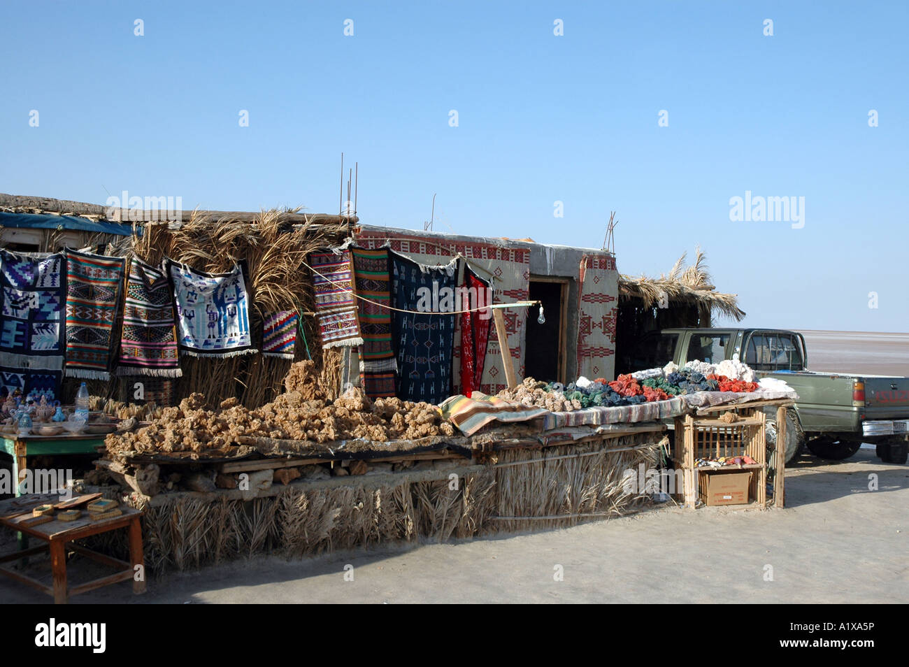Souvenirs stall on the roadside of causeway crossing Chott el Jerid lake in Tunisia - Stock Image