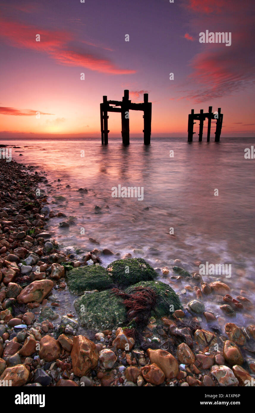 The remains of a D-Day pier, known as the Dolphins, stand in the Solent at Lepe beach - Stock Image