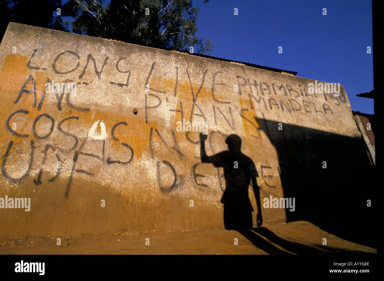 SHADOW OF FIGURE WITH RAISED CLENCHED FIST ON WALL WITH GRAFFITI FOR POLITICAL PARTIES WESTERN TRANSVAAL SOUTH AFRICA 1991 - Stock Image