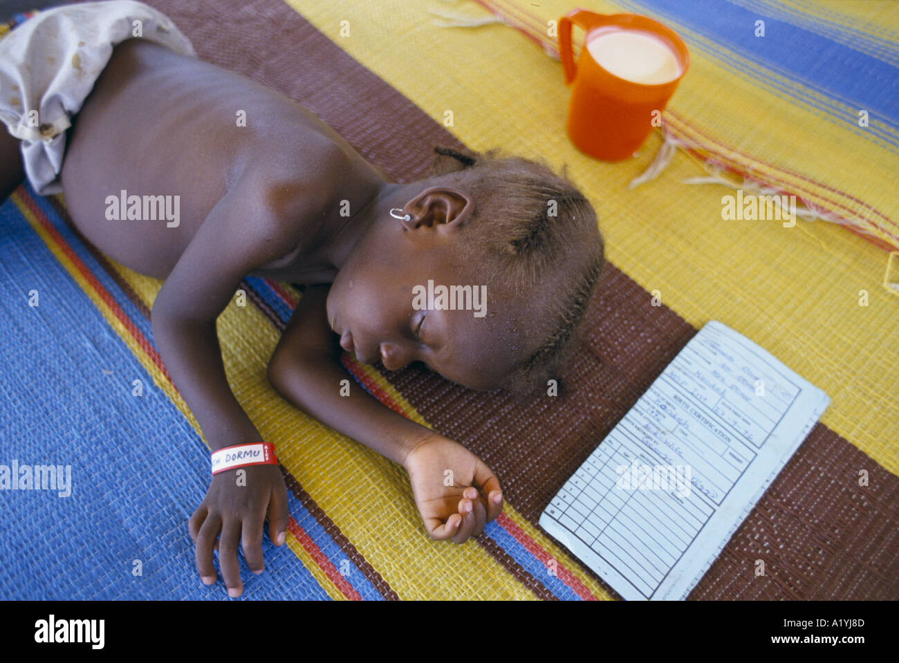 CHILD SLEEPING AT OXFAM FEEDING CENTRE IN SINJE LIBERIA OCTOBER 1996 - Stock Image