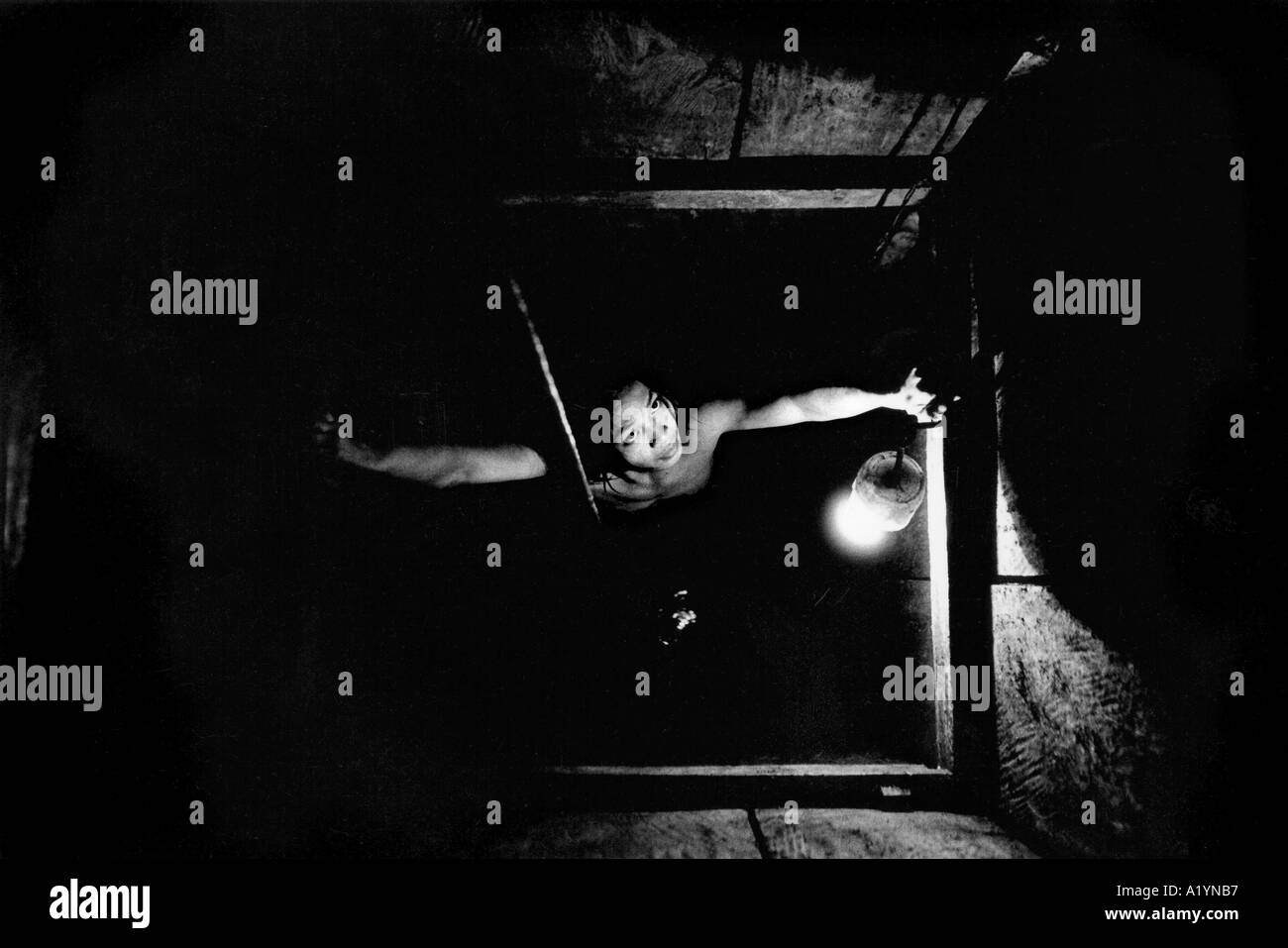 A young gold miner of small build is lowered down a hole up to 100 metres. - Stock Image