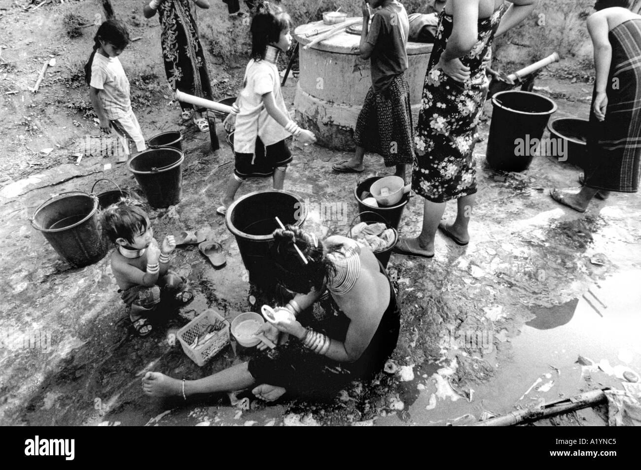 Paduang women and young Paduang girls wash up by the village well in Nai Soi - Stock Image