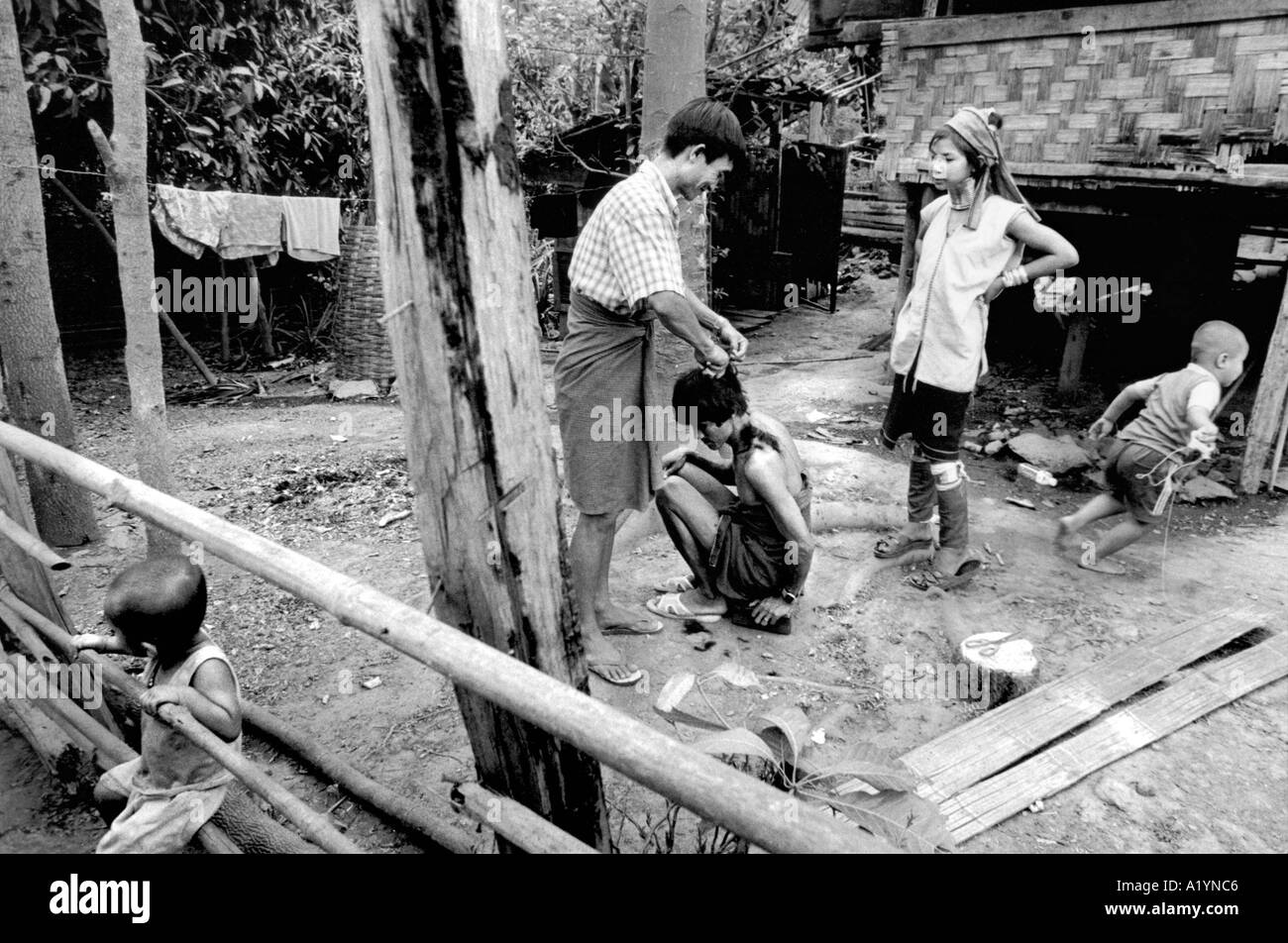 A young Paduang man gets a haircut from his father in the garden of their house in Hauy Pukeng village - Stock Image