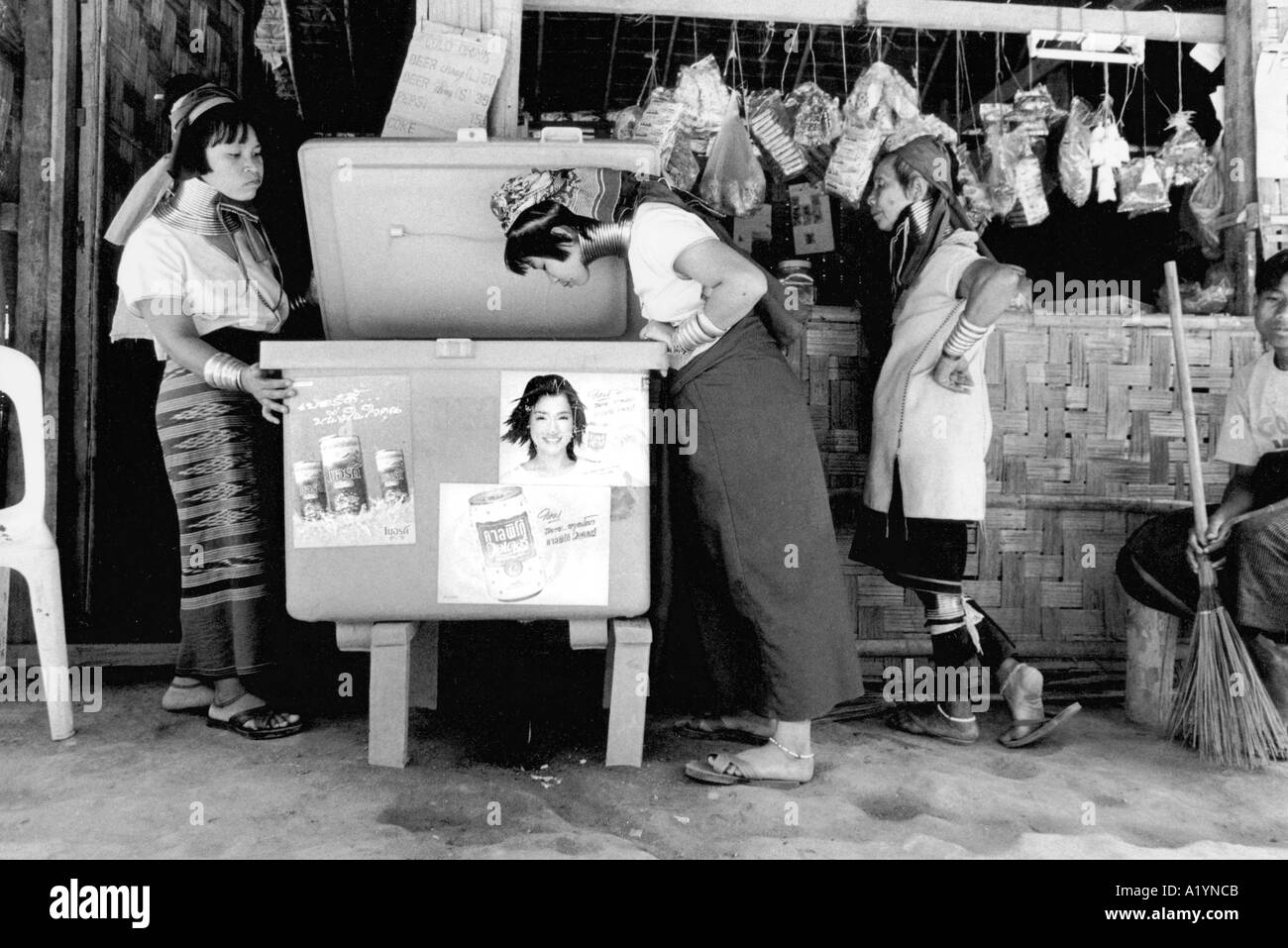 Long necked women looking into a chest in front of a local shop - Stock Image
