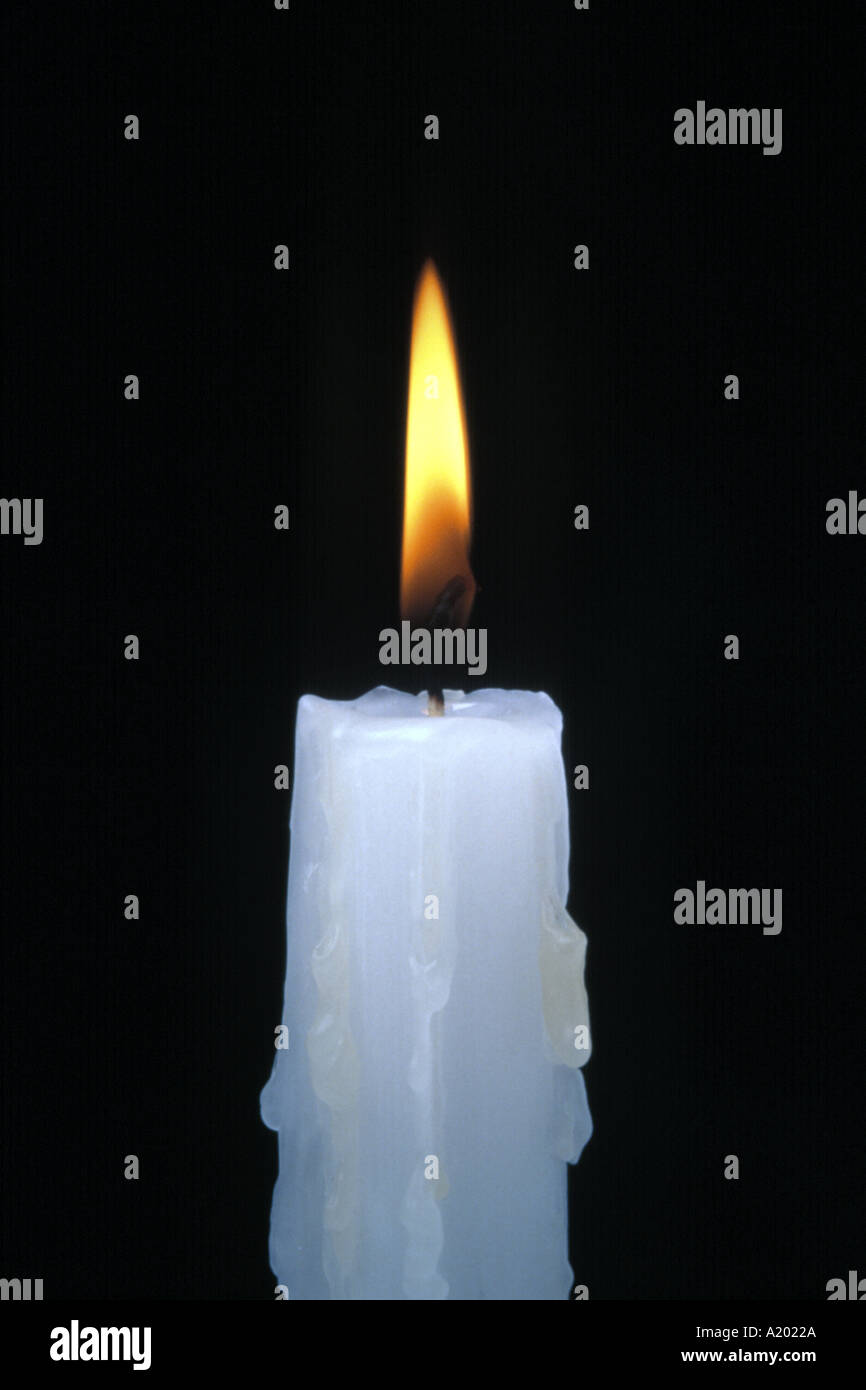 white wax candle burning with yellow flame against a black background - Stock Image