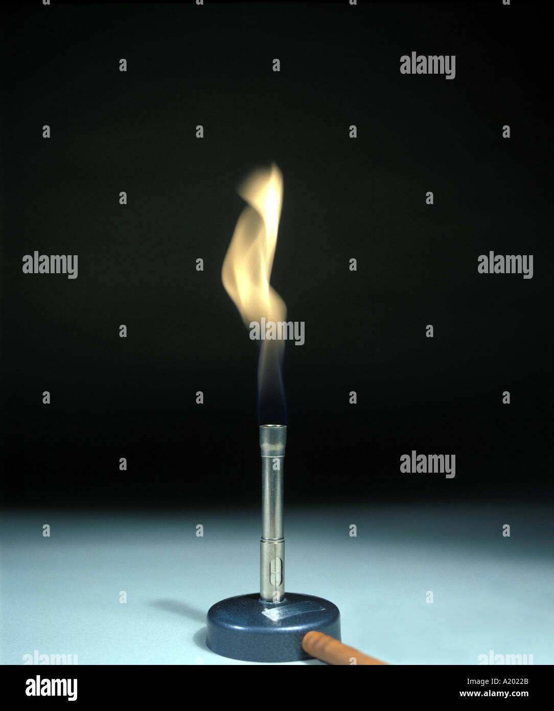 bunsen burner has a sooty yellow flame when the air hole is closed - Stock Image