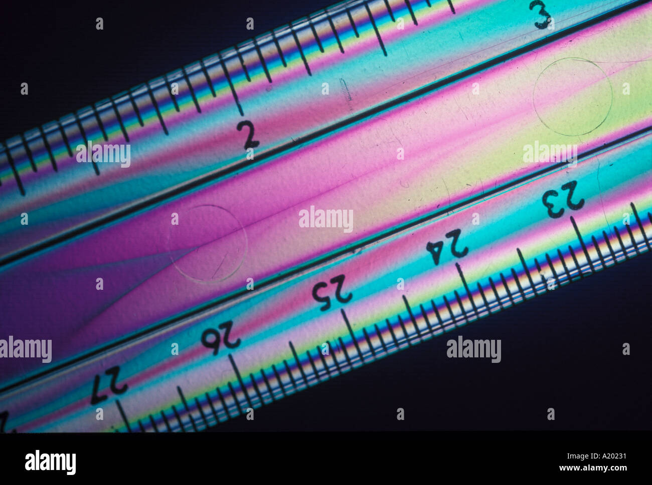 clear plastic ruler in polarised light produces colours related to stress - Stock Image