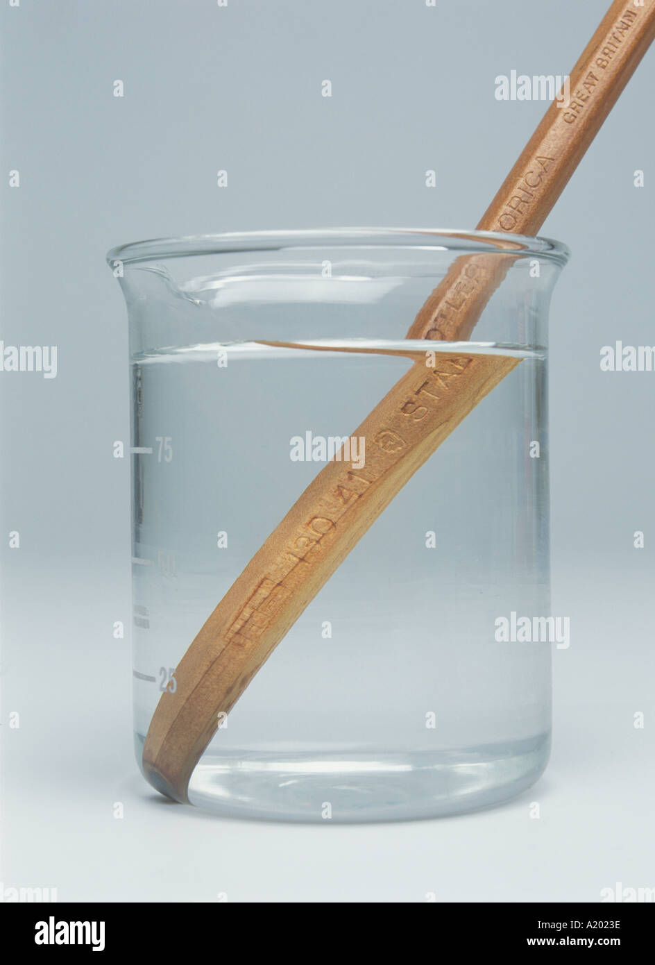 pencil appears bent in water due to refraction - Stock Image