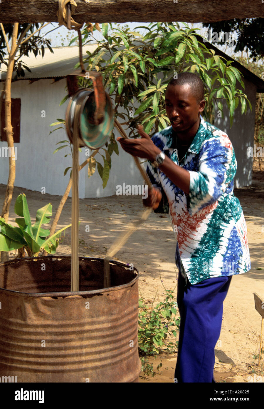 Local man drawing water from a well Tanji - Stock Image