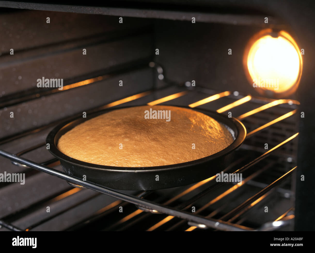 a cake in oven after baking see A23221 for before baking - Stock Image