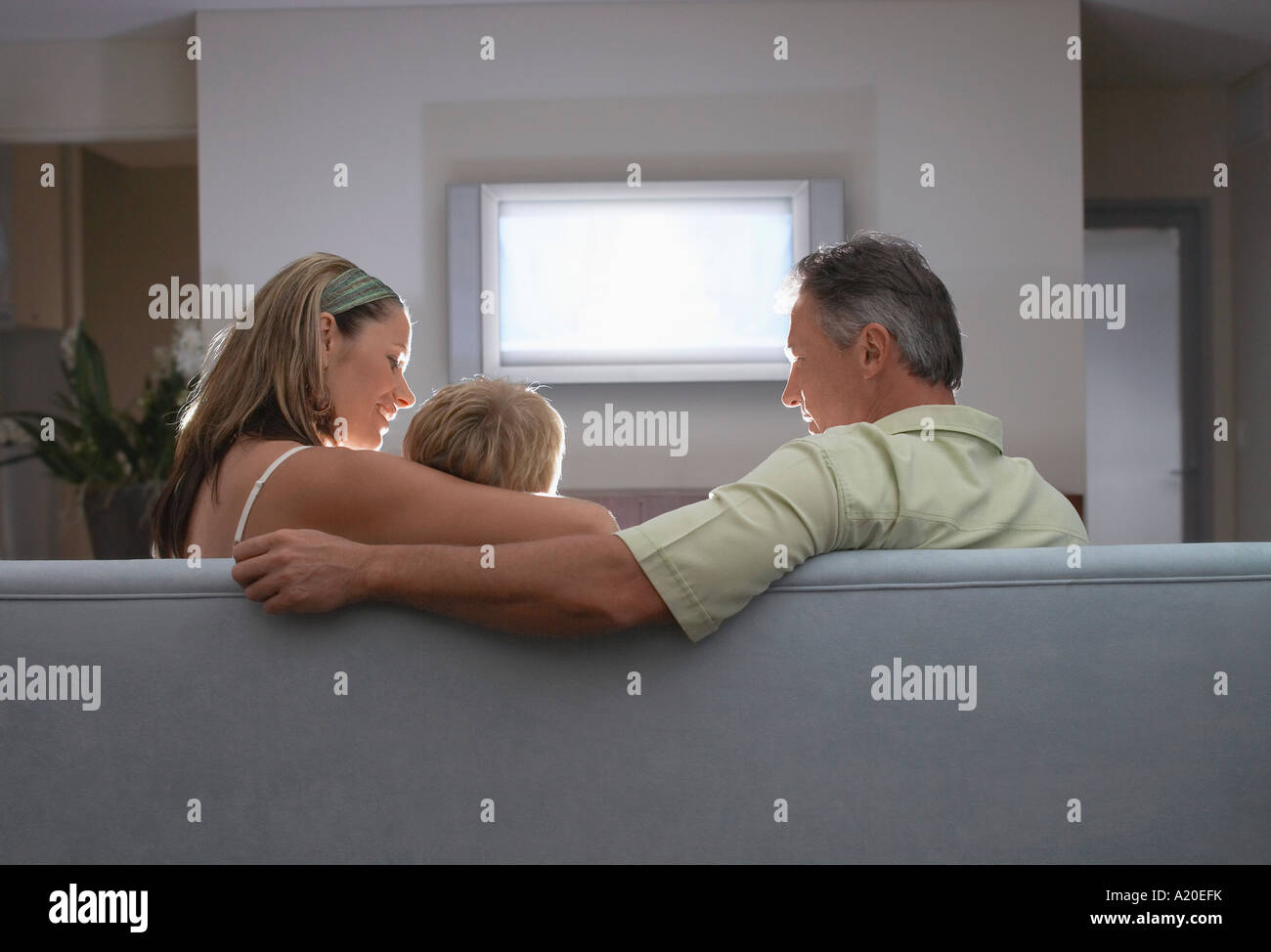 Parents sitting on sofa, arm around son, Watching TV, back view - Stock Image