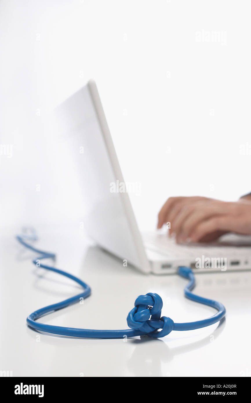 Woman using lap top with knotted cable in studio, close up on knot - Stock Image