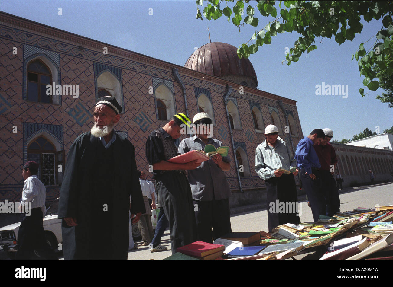 Men arriving for prayers at the Haji Yakoub mosque, Dushanbe stop to read, buy books of Islamic texts and teachings, Tajikistan - Stock Image