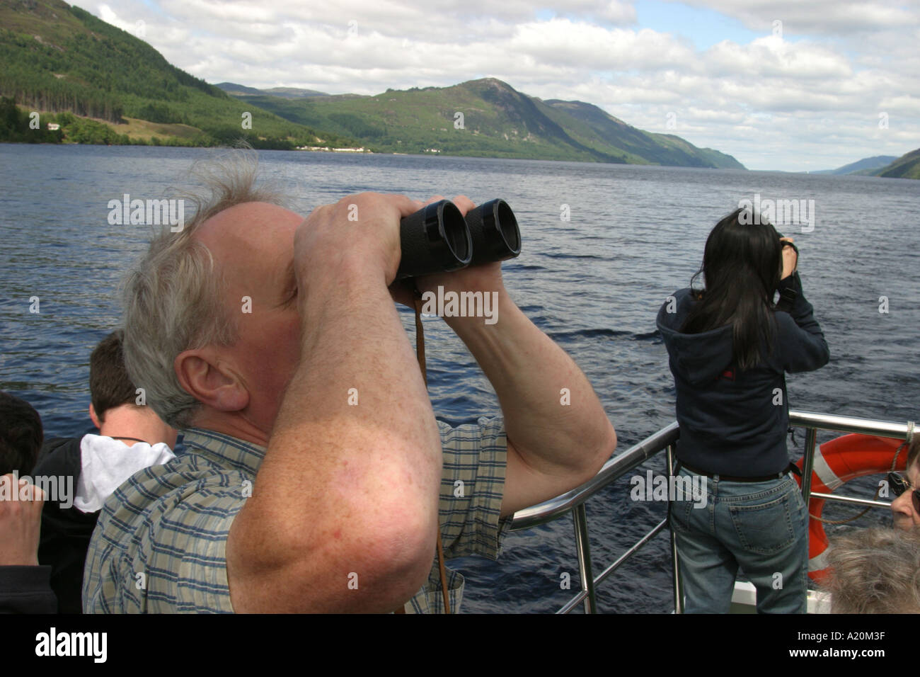 Tourists on a day trip pleasure cruiser on Loch Ness looking for Nessie the Loch Ness Monster, Scotland - Stock Image