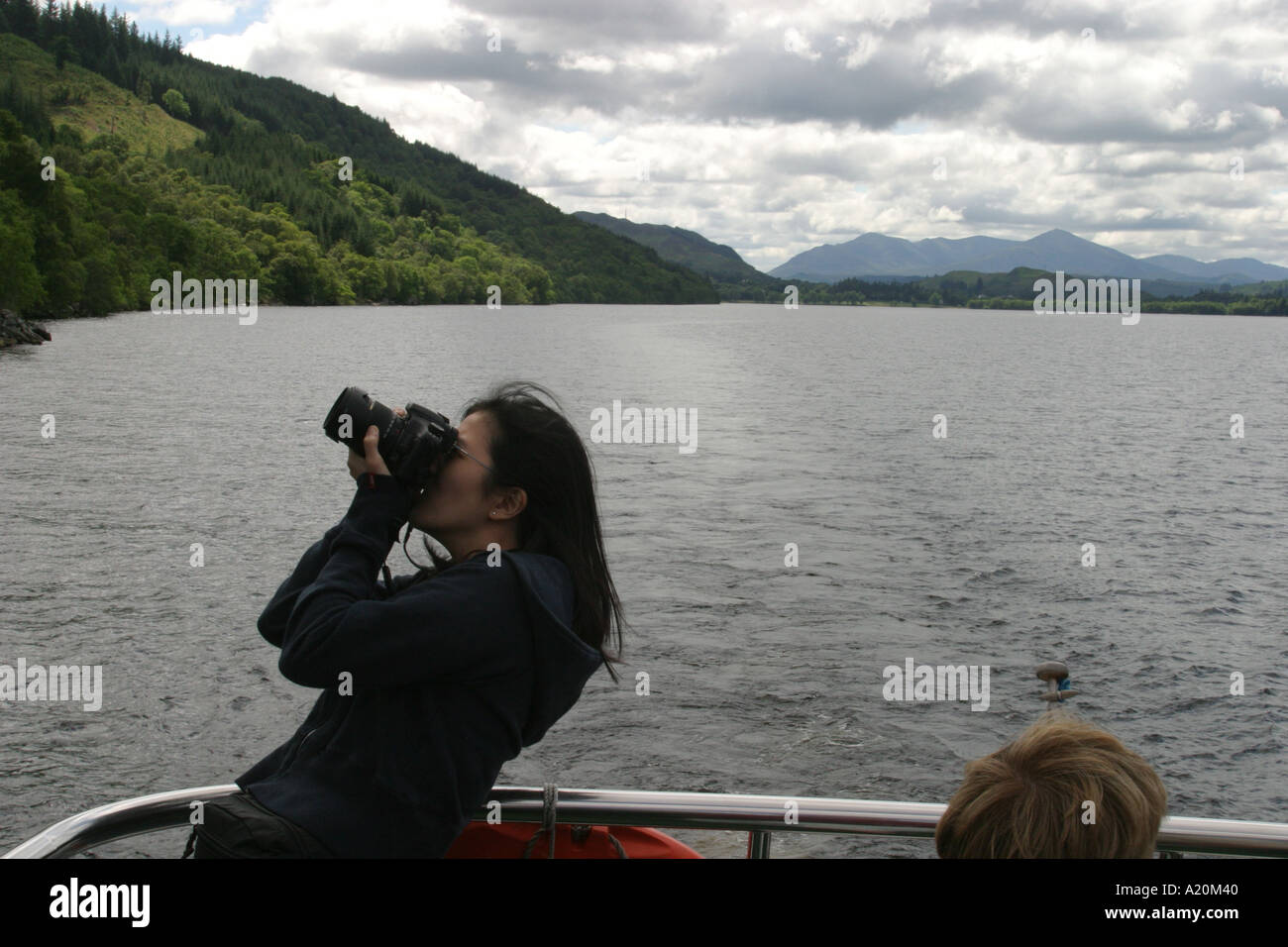 A tourist on a pleasure cruiser boat tour of Loch Ness tries to photograph the scenery, Scotland. - Stock Image