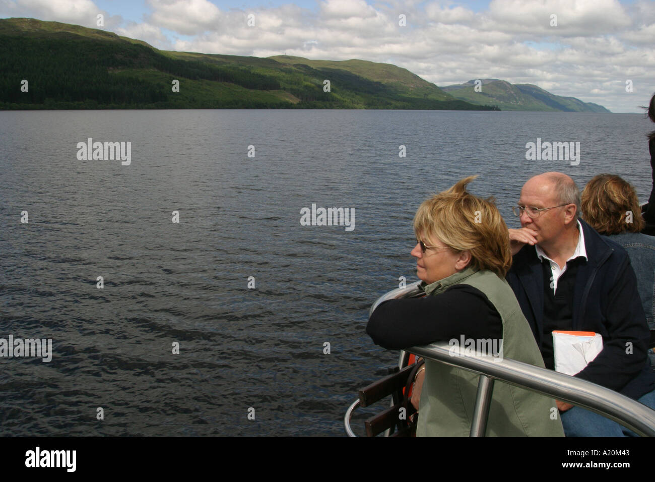 Tourists on a pleasure cruiser boat tour of Loch Ness keep an eye open for the Nessie the Loch Ness Monster, Scotland - Stock Image