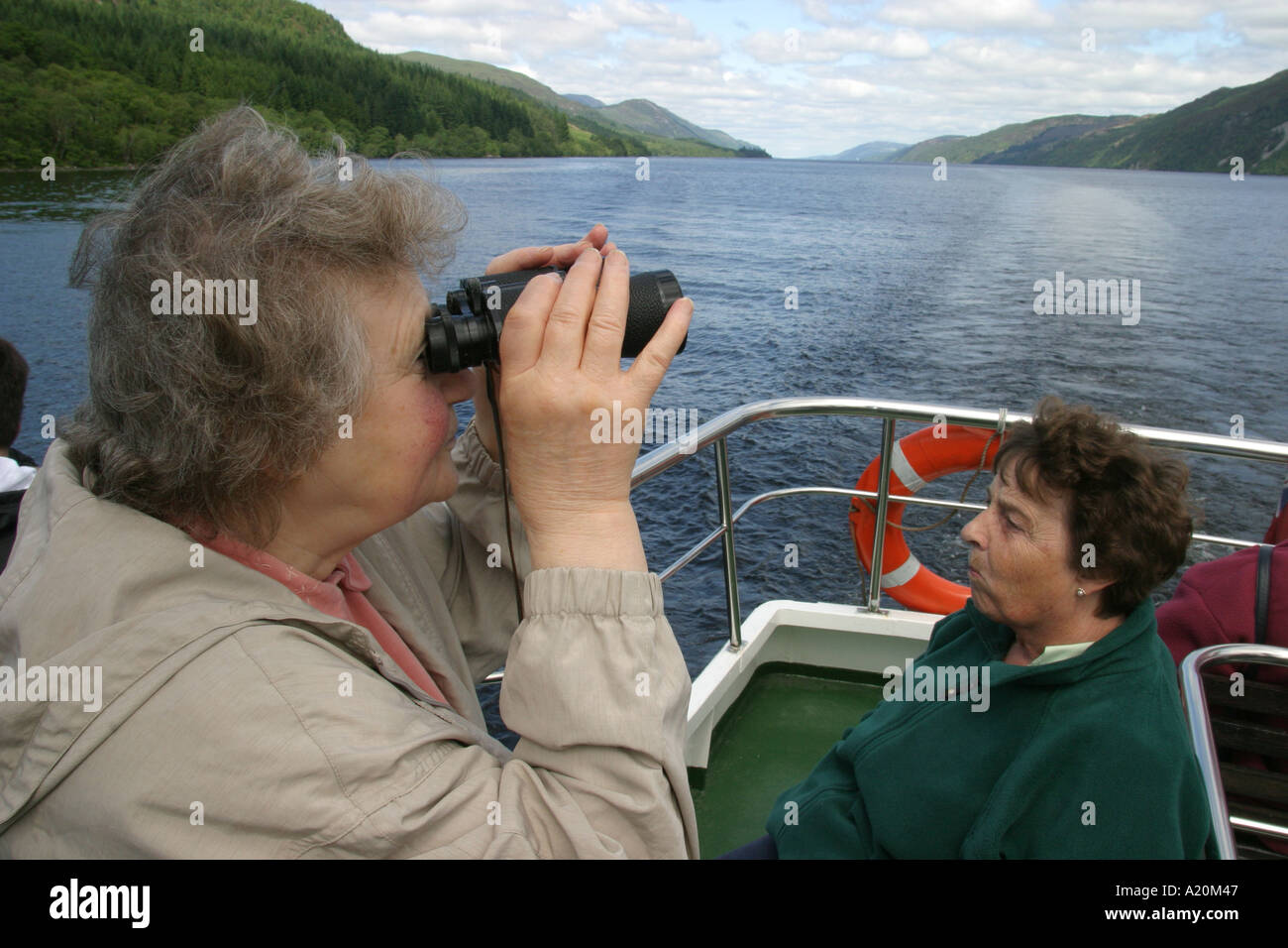 Women sitting on a day trip pleasure cruiser on Loch Ness hoping to see Nessie the Loch Ness Monster, Scotland - Stock Image