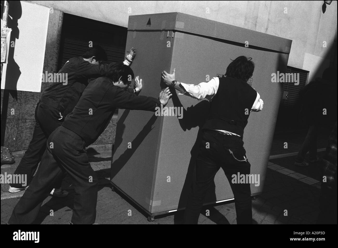 Delivery men push a large box in a street in the Shibuya district of the city, Tokyo, Japan - Stock Image