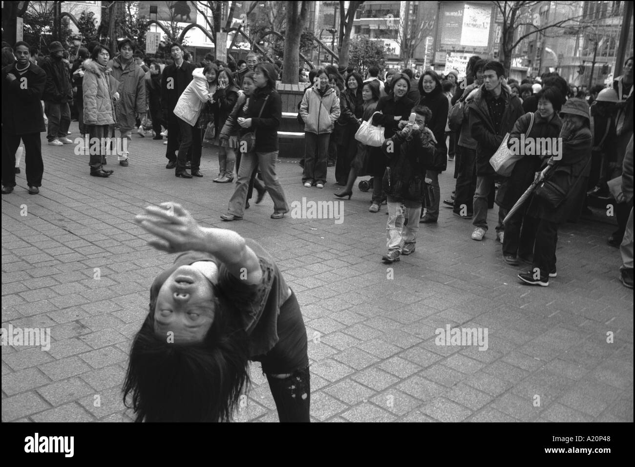 A woman dances as if possessed to the amusement and bewilderment of passerbys outside Shibuya train station, Tokyo, japan - Stock Image