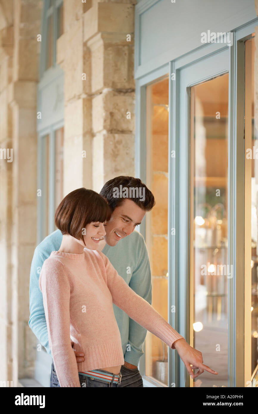 Couple looking in shop window, half length - Stock Image