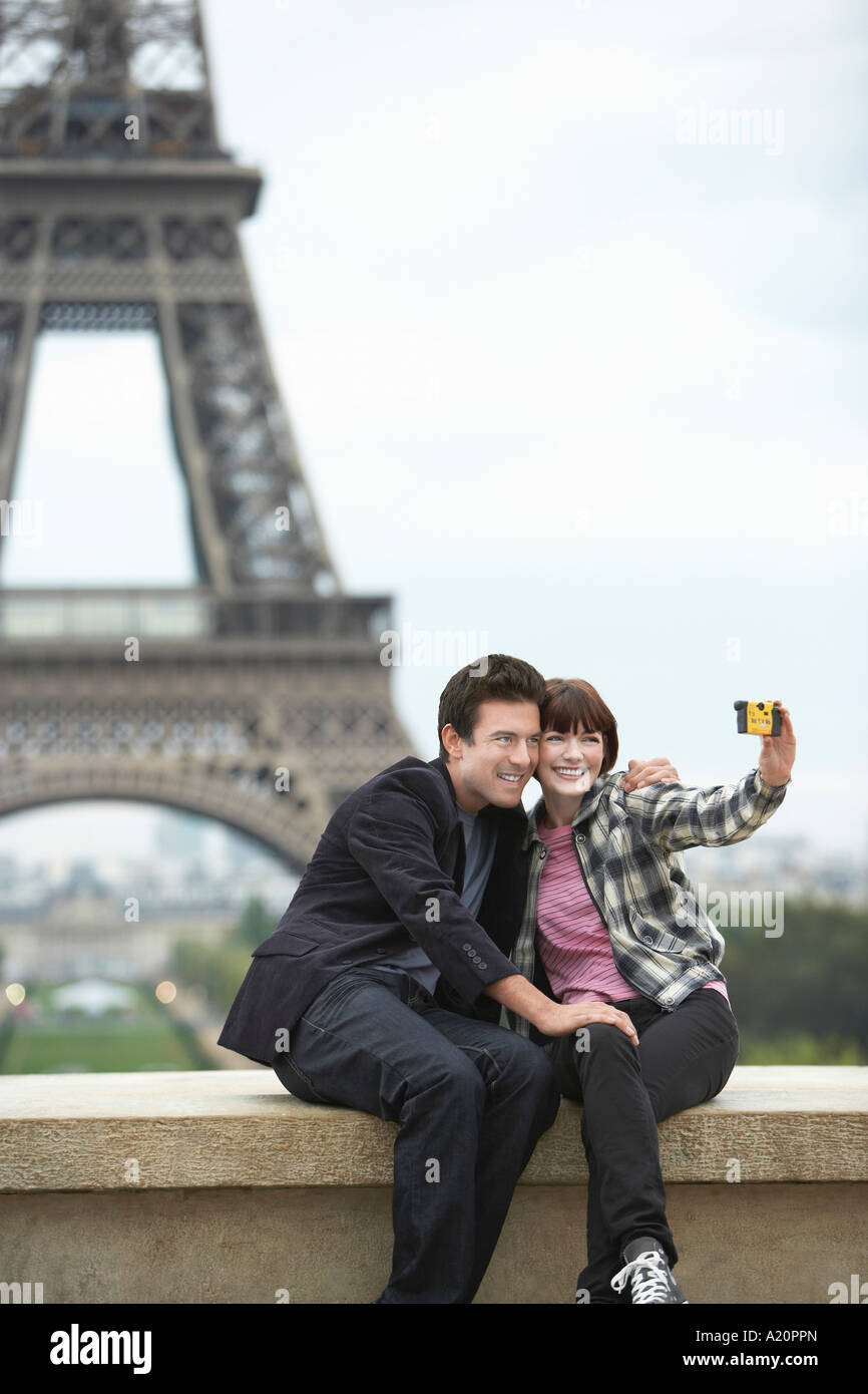 France, Paris, couple taking self portrait  in front of Eiffel Tower - Stock Image