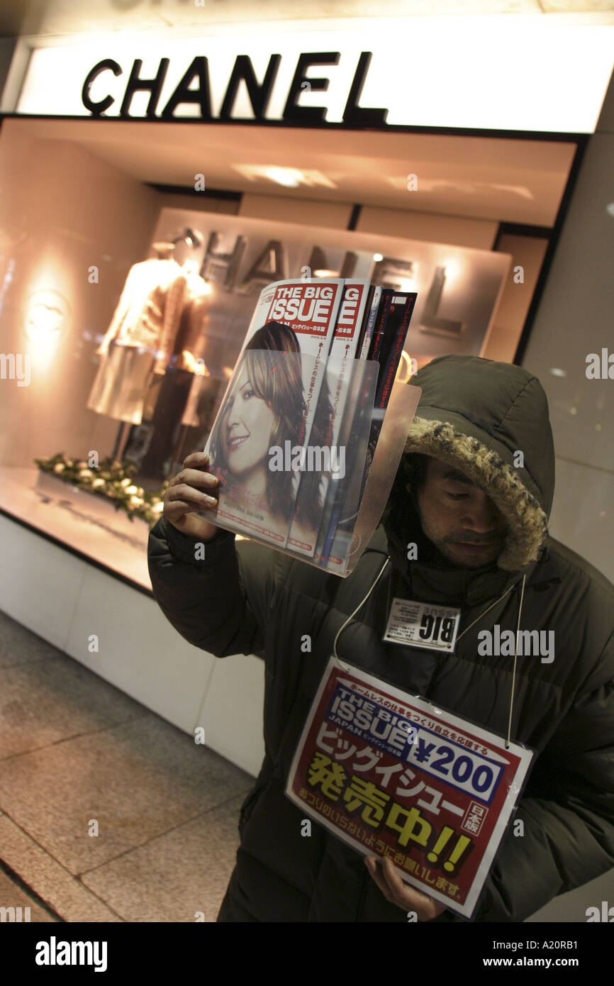 Japanese homeless man selling The Big Issue in front of Chanel fashion store, Tokyo, Japan. - Stock Image