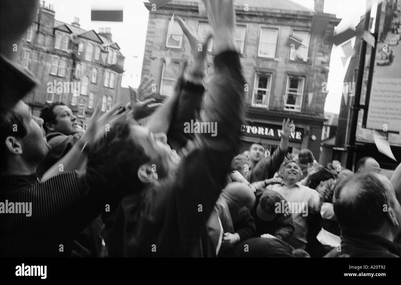 Men fighting to catch sachets of snuff tobacco, Hawick Common Riding week festivities, Scotland, UK Stock Photo