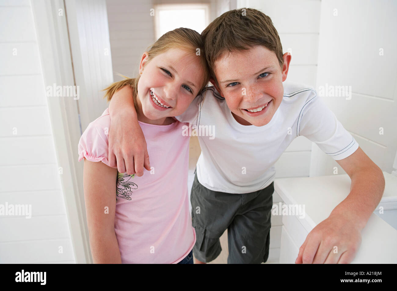 Young boy with arm around young girl in white room Stock Photo