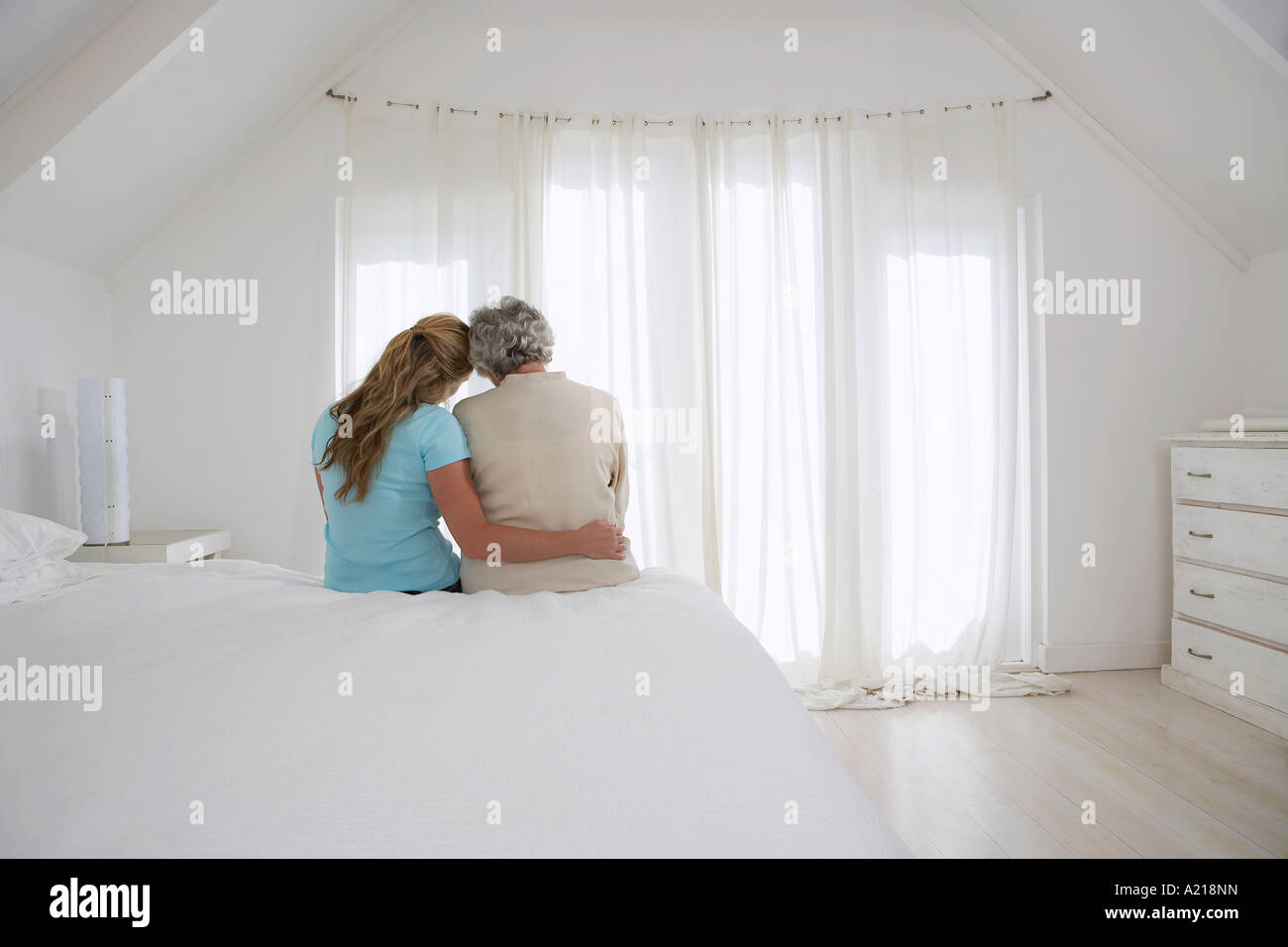 Rear view of adult daughter with her arm around mother in white bedroom - Stock Image