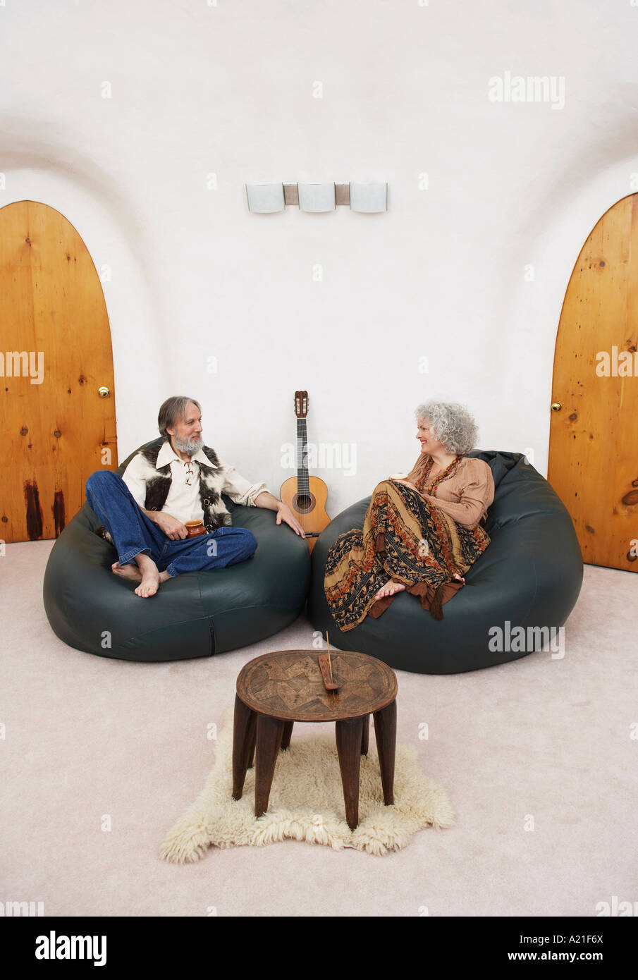 Couple Sitting in Bean Bag Chairs in Living Room Stock Photo