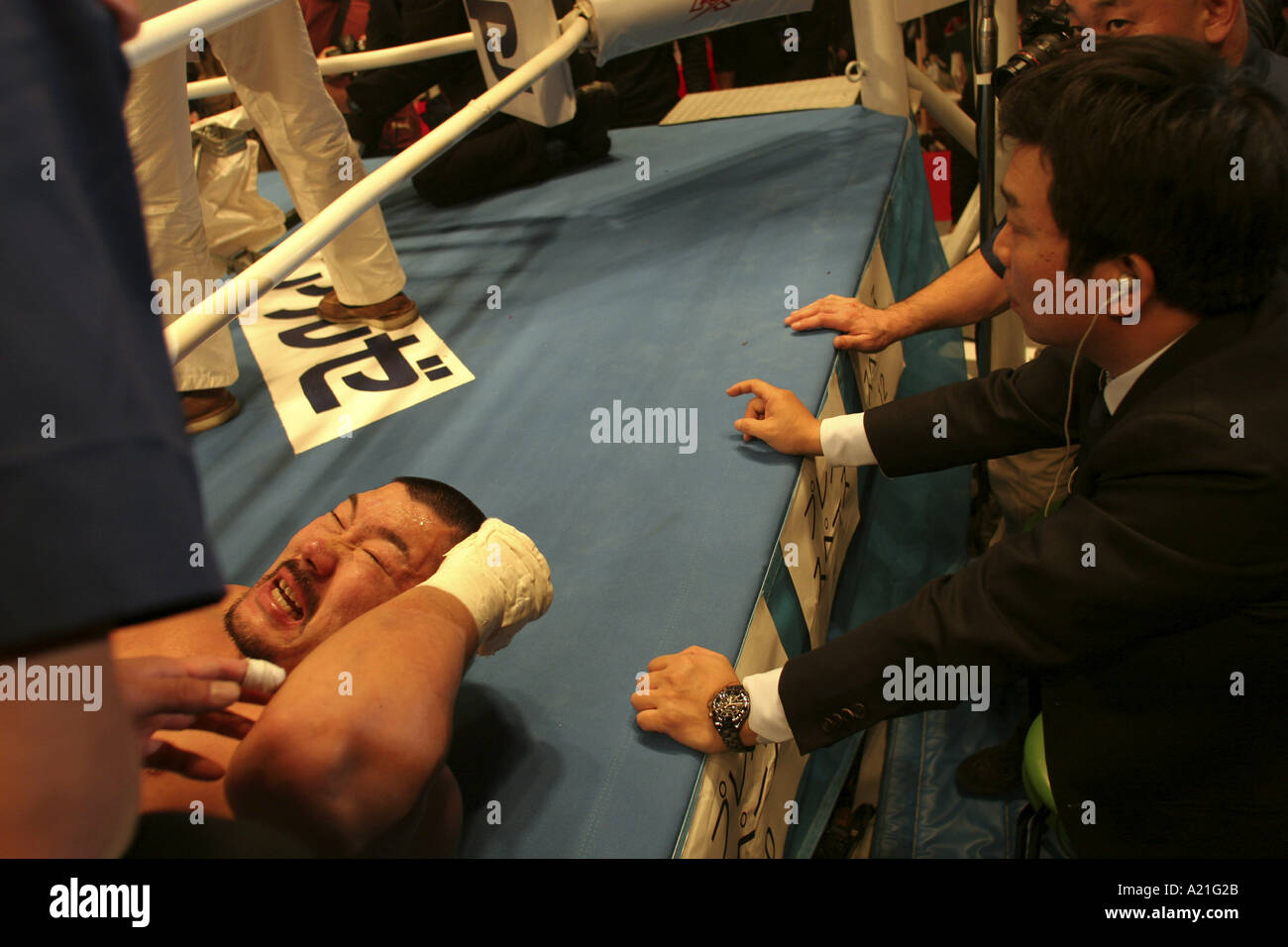 K-1 fighter winces in pain in the ring after defeat by knock-out, Tokyo, Japan - Stock Image