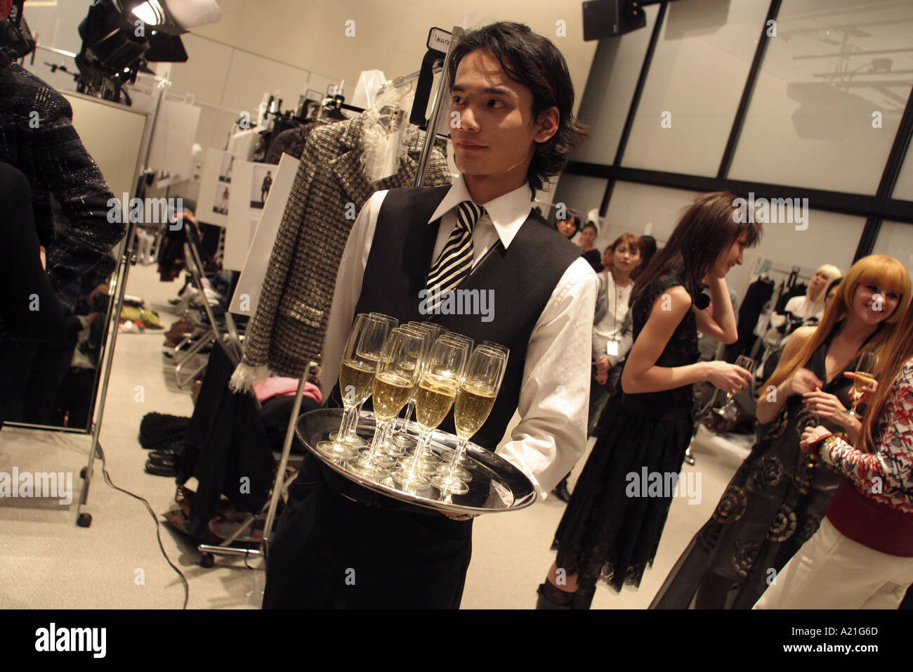 Waiter and models backstage with champagne after Chanel fashion show, Tokyo, Japan. - Stock Image