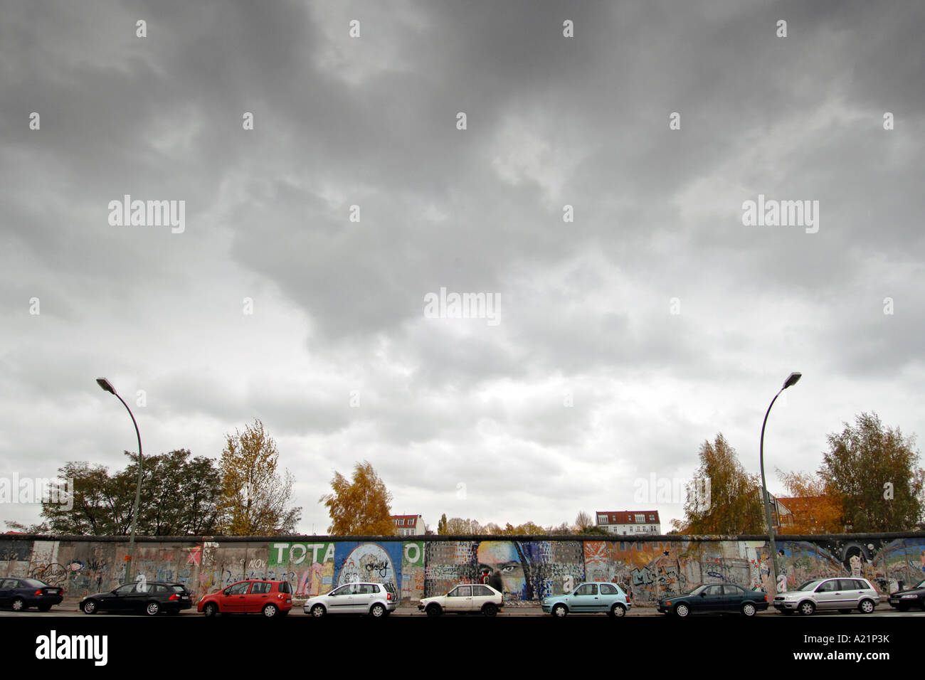 Cars parked along the East Side Gallery, a preserved commemorative section of the Berlin wall in Germany. - Stock Image