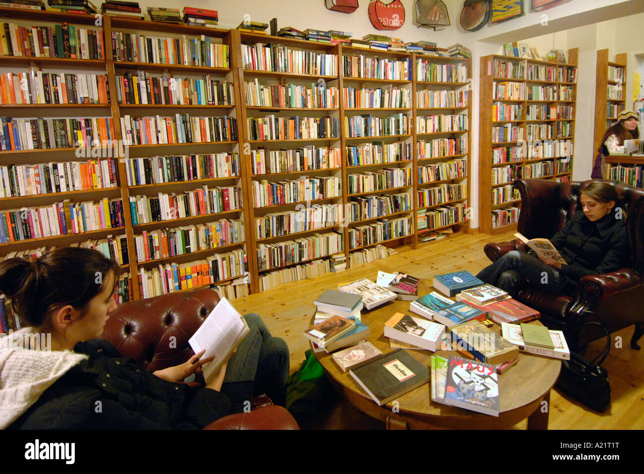 Two girls reading inside the St Georges English Bookshop in East Berlin. - Stock Image