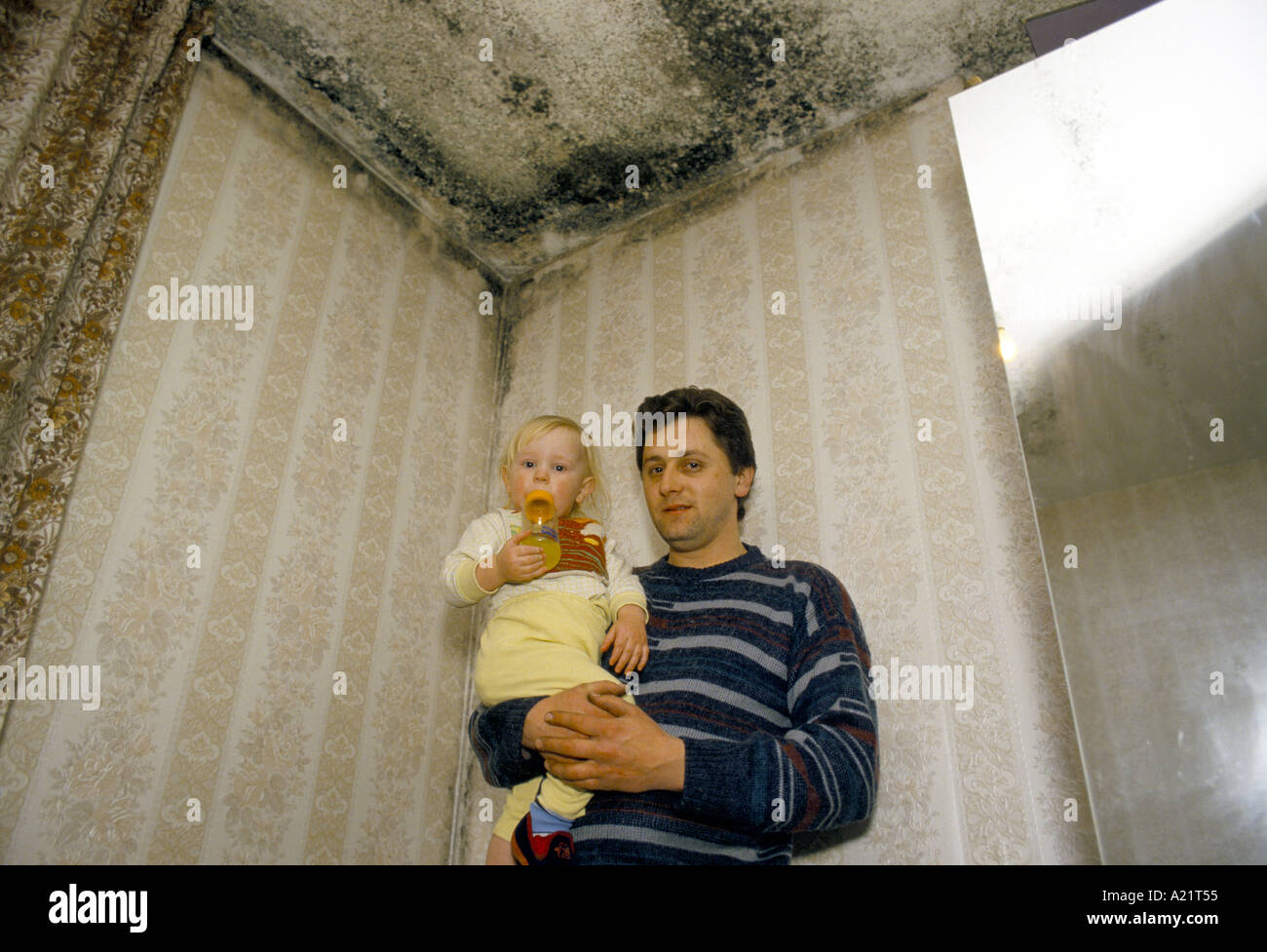 A father and his child forced to live in only  one room because of damp in all the other   rooms, Tower Hamlets, London, UK - Stock Image