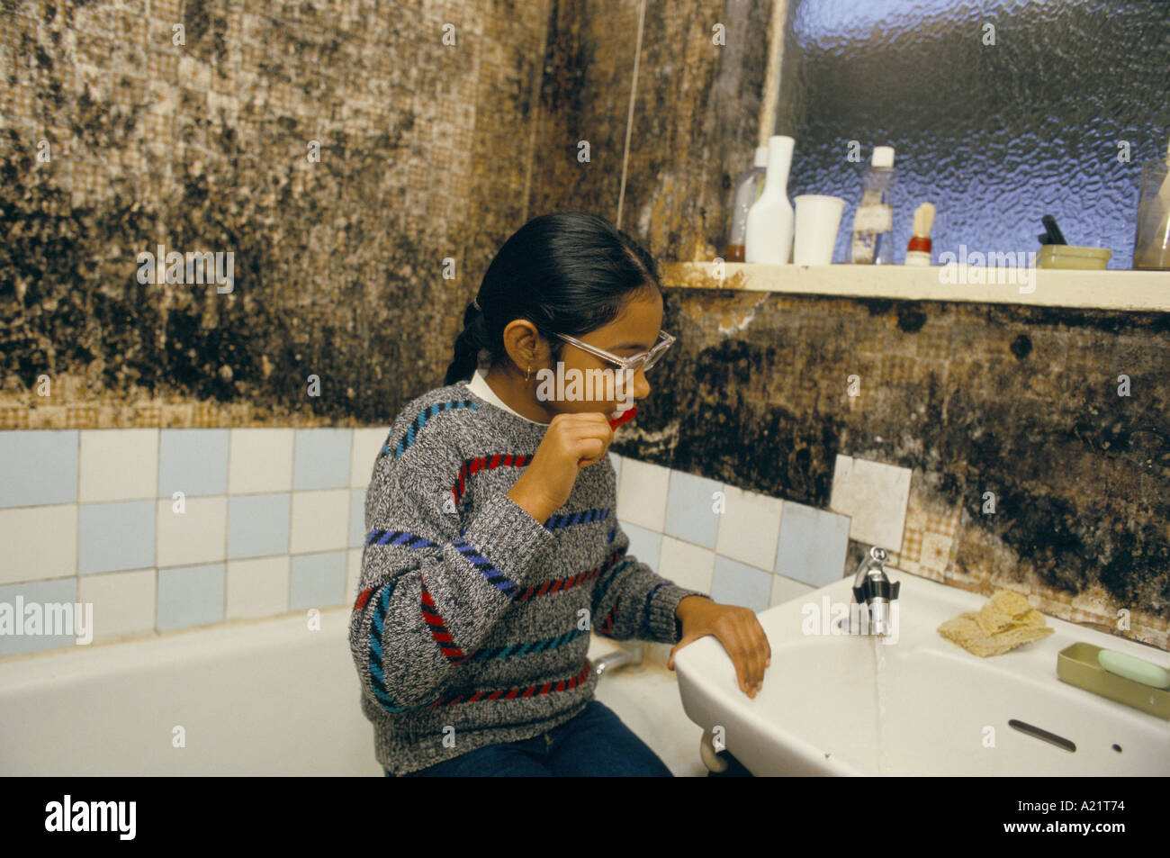 An Asian girl brushing her teeth in a bathroom  with  mouldy walls, Tower Hamlets, London, UK - Stock Image