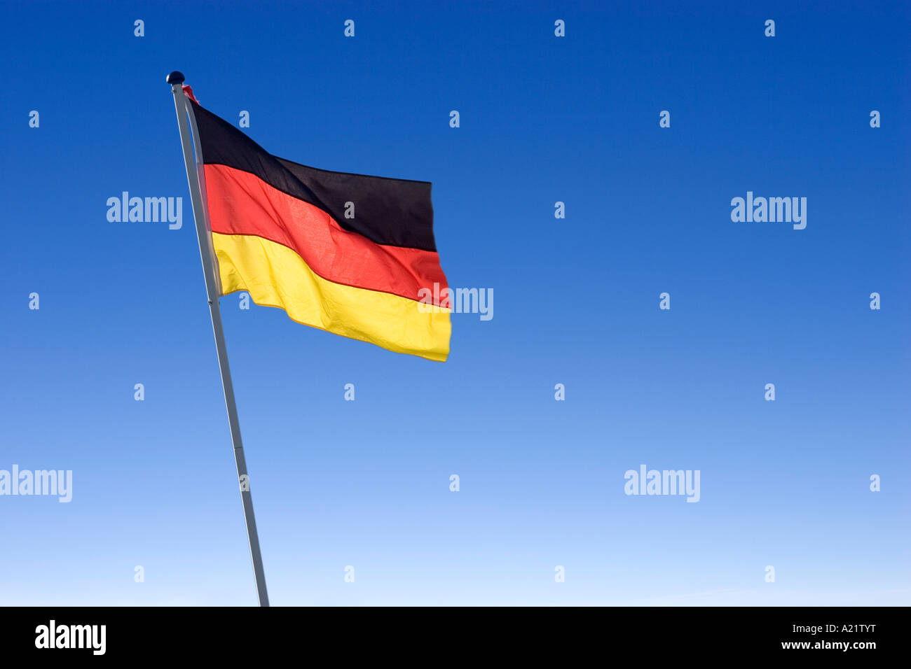 German National Flag waving in blue sky fine weather Germany - Stock Image