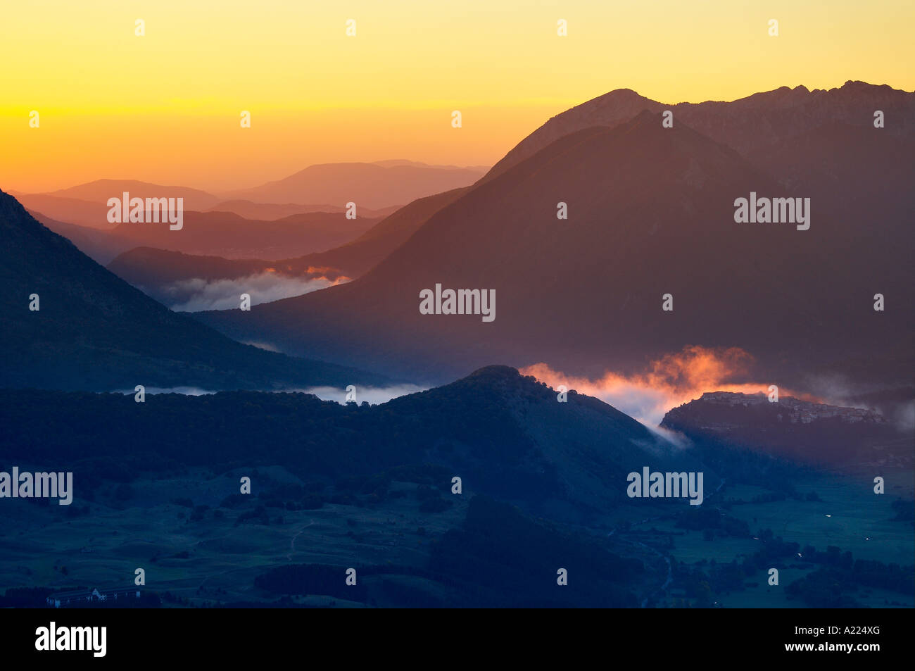 mist swirling around the village of Opi picked out by a shaft of dawn light, Abruzzo National Park Abruzzo Italy Stock Photo