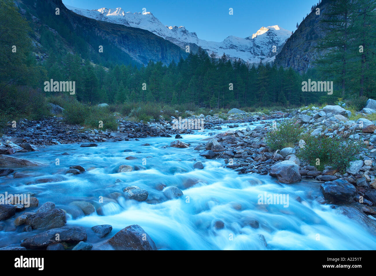 River in the Valnontey with the snow clad peaks of the Parco Nazionale del Gran Paradiso Valle d Aosta Italy NR - Stock Image