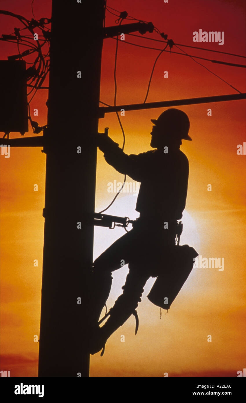 Worker on Power Pole - Stock Image