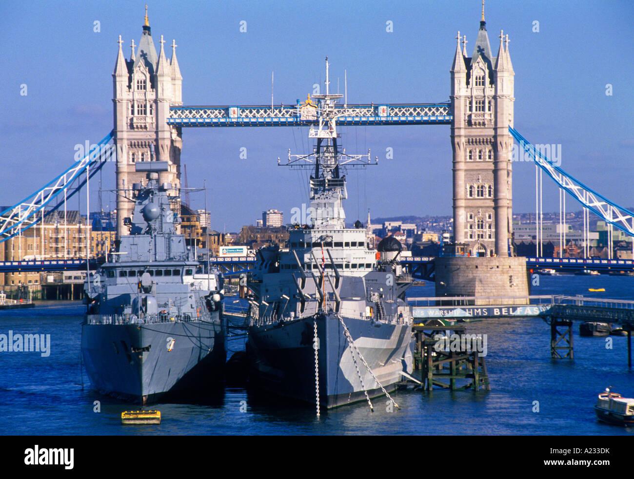 England UK London England Historic Tower Bridge on the Thames River Two Navy Battleships Moored Europe - Stock Image