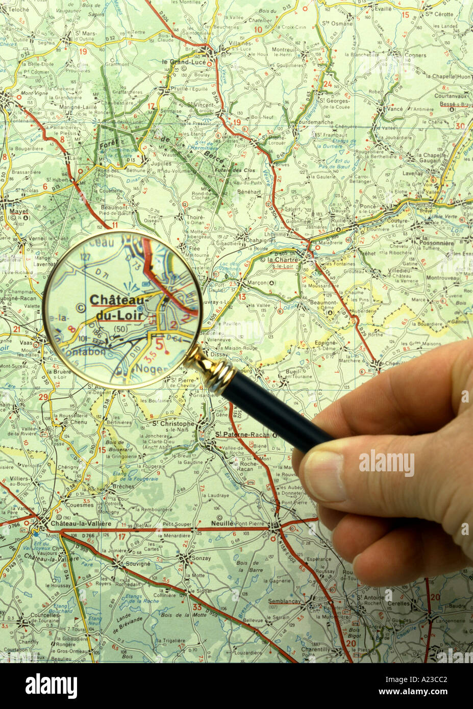 a magnifying glass being used to read a French map - Stock Image