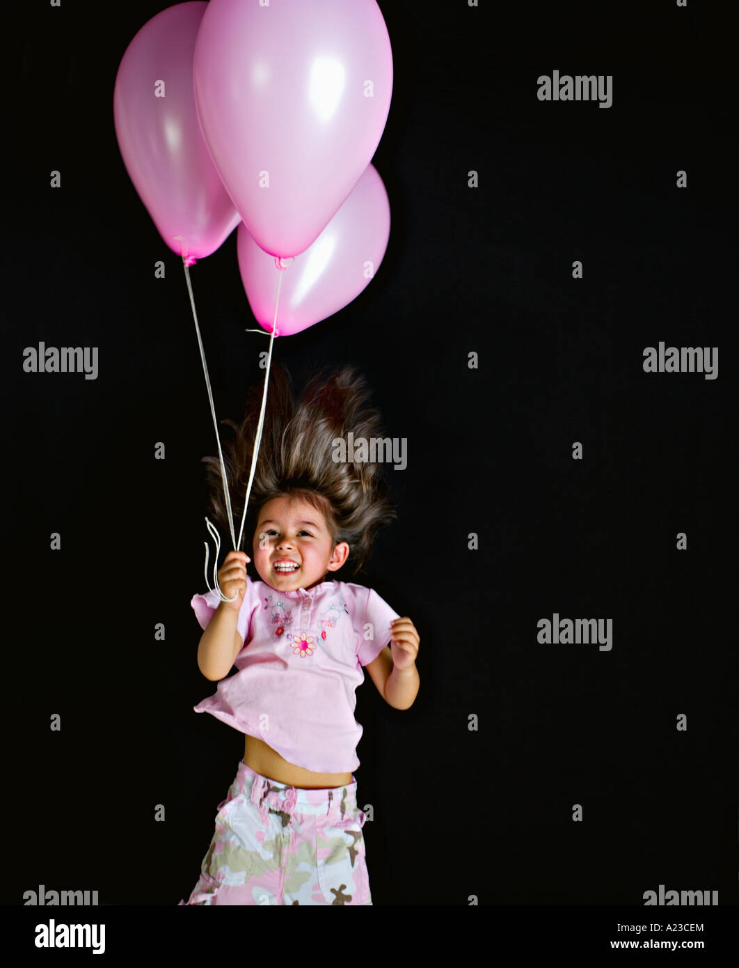 Girl swings through air with pink balloons - Stock Image