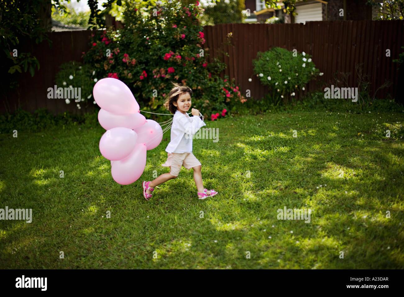 Girl runs with pink balloons - Stock Image