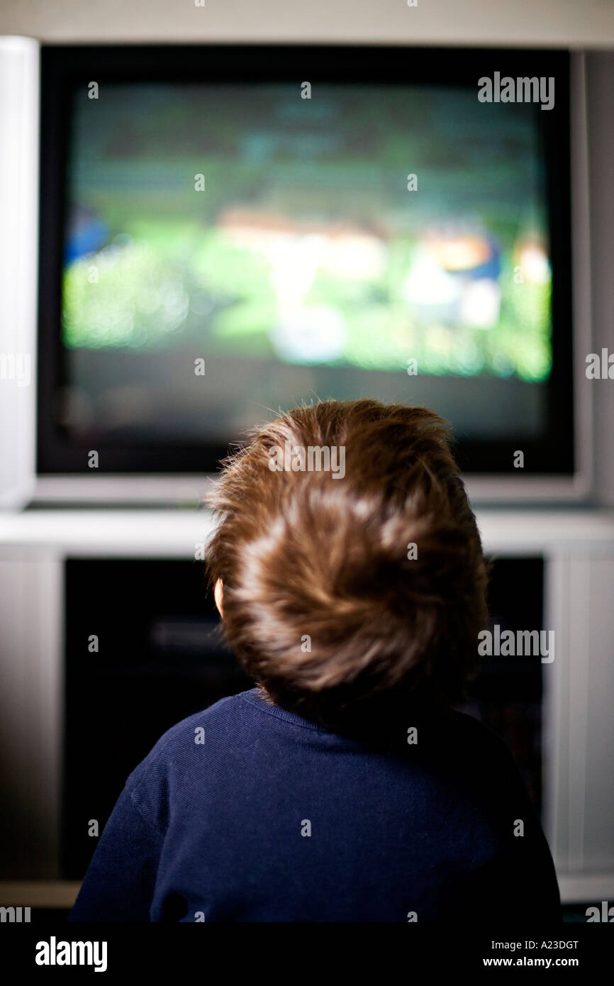 Boy aged 4 years entranced sits in front of the TV - Stock Image