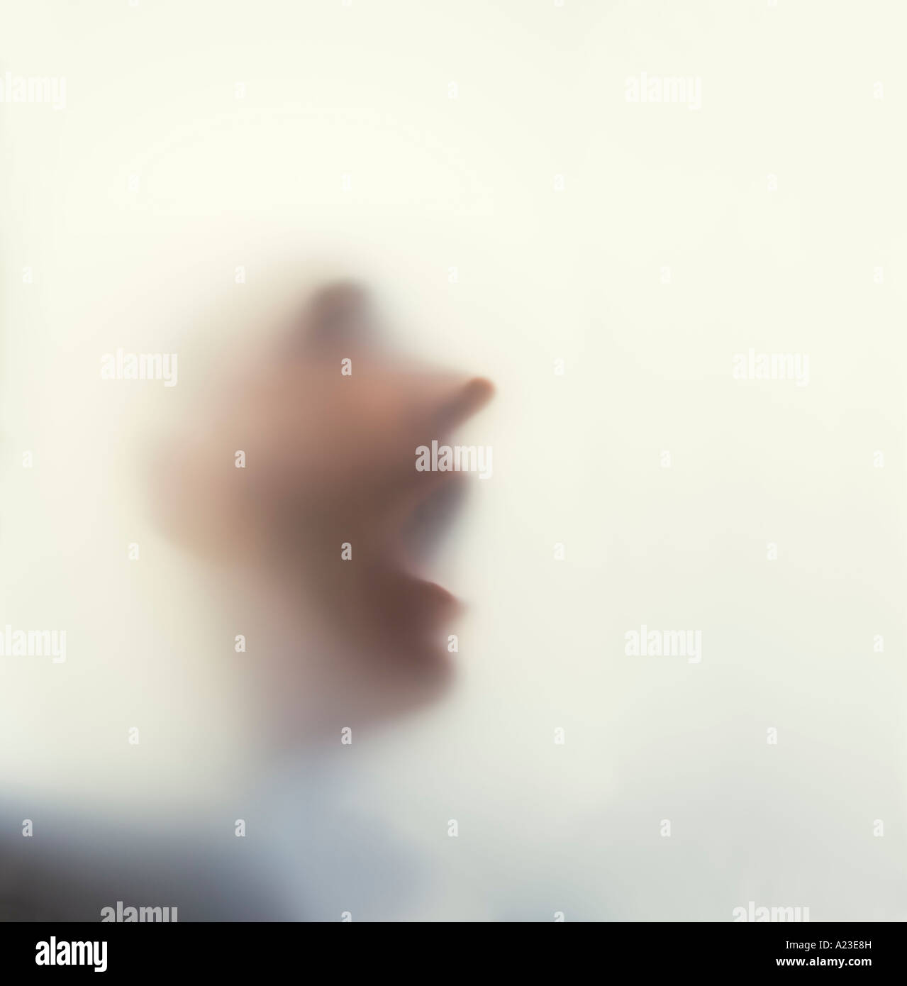 Man with face against frosted glass - Stock Image
